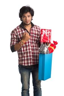 Jonge man rakhi tonen op zijn hand met boodschappentassen en geschenkdoos ter gelegenheid van het raksha bandhan-festival.
