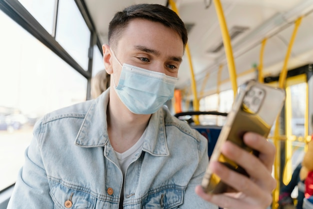 Jonge man reizen met de stadsbus met smartphone