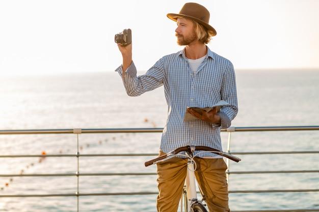Jonge man reizen op de fiets over zee op zomervakantie aan zee op zonsondergang, kaart sightseeing nemen foto op camera houden