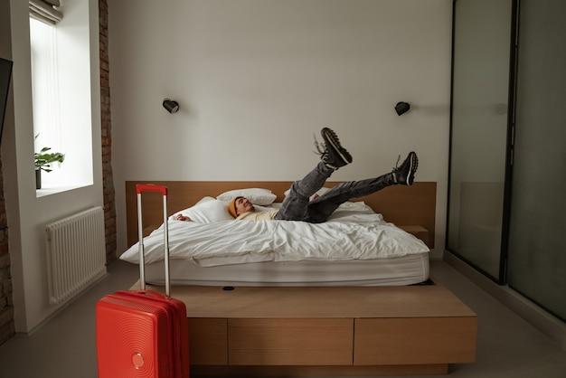 Jonge man reiziger met bagage springen op bed in hotelkamer op zomervakantie. cool man in casual kleding.