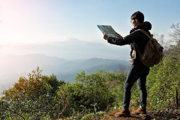 Jonge man reiziger met kaart rugzak ontspannen buiten met rotsachtige bergen op achtergrond zomervakanties en lifestyle wandelen concept