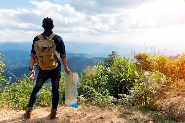 Jonge man reiziger met kaart rugzak ontspannen buiten met rotsachtige bergen op de achtergrond zomer vakanties en lifestyle wandel concept