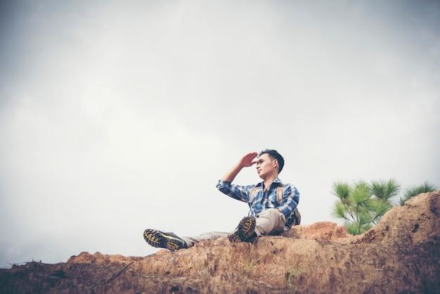 Jonge man reiziger met rugzak ontspannen buiten met rotsachtige bergen op achtergrond zomervakanties en lifestyle wandelen concept.