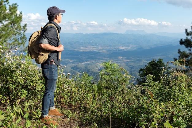 Jonge man reiziger met rugzak ontspannen buiten met rotsachtige bergen op achtergrond zomervakanties en lifestyle wandelen concept