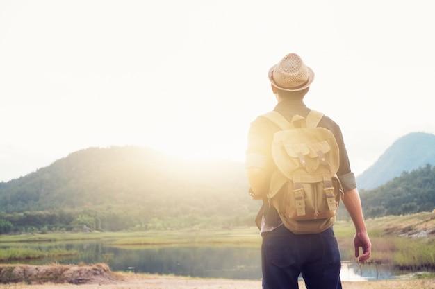 Jonge man reiziger met rugzak ontspannen buiten.