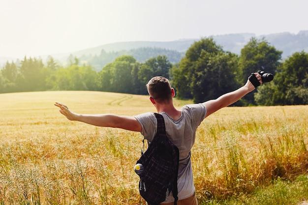 Jonge man reiziger spreidt zijn armen en kijkt naar het gouden tarweveld