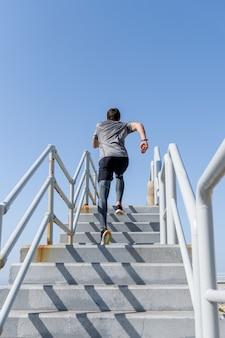 Jonge man rent naar buiten met heldere lucht, draagt sportkleding