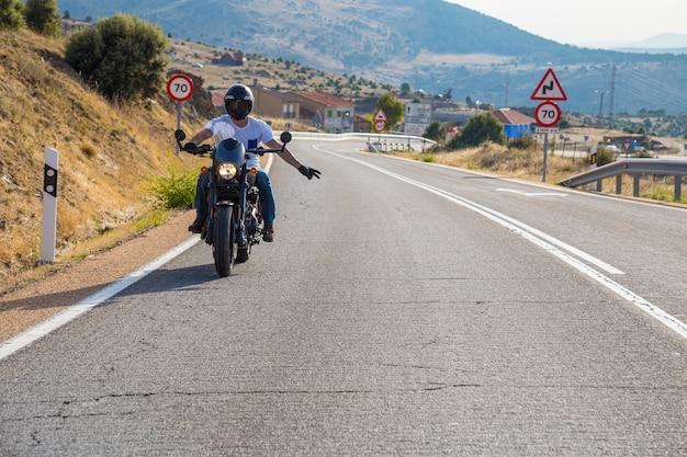 Jonge man rijden op een motorfiets op de weg in de bergen in zonnige dag terwijl het doen van de fietser groet.