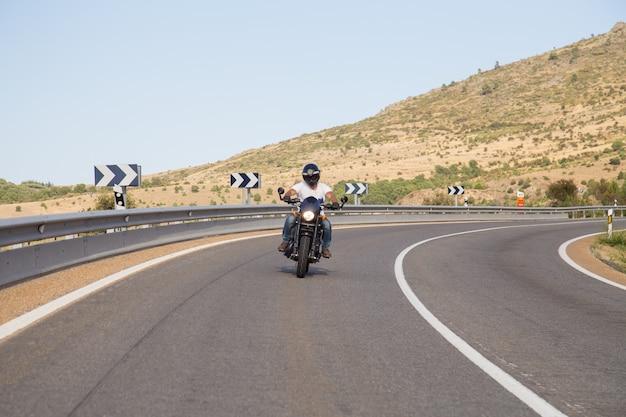 Jonge man rijden op een motorfiets op weg in een bocht in de bergen op zonnige dag.