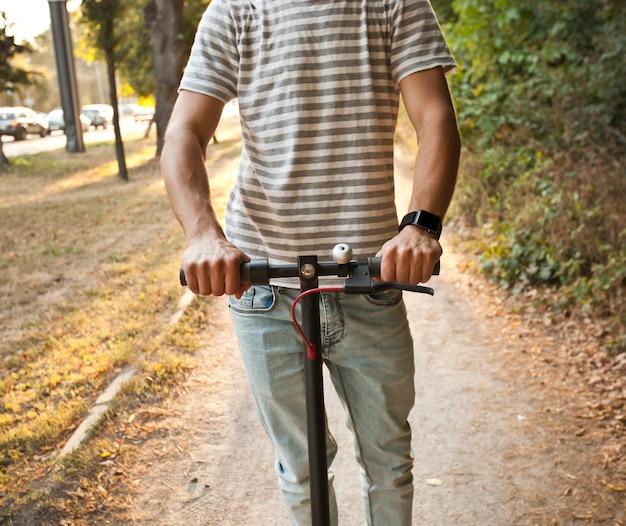 Jonge man rijdt op de elektrische scooter door de avondstad door de paden