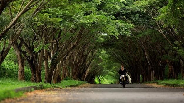 Jonge man rijdt op een motorfiets met een surfplank