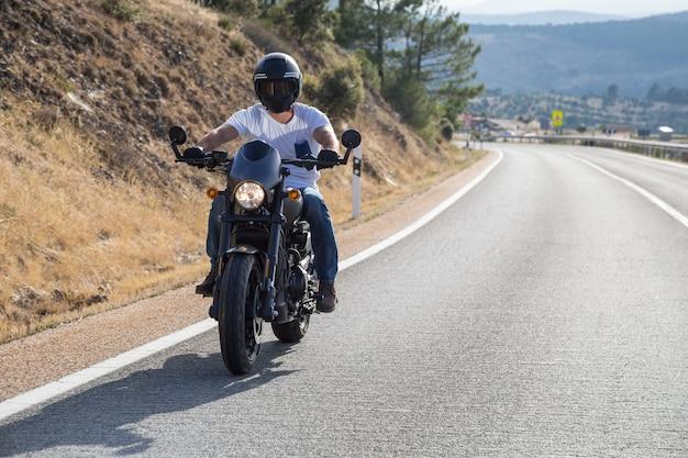Jonge man rijdt op een motorfiets op weg in de bergen in zonnige dag
