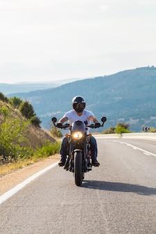 Jonge man rijdt op een motorfiets op weg in de bergen op zonnige dag.