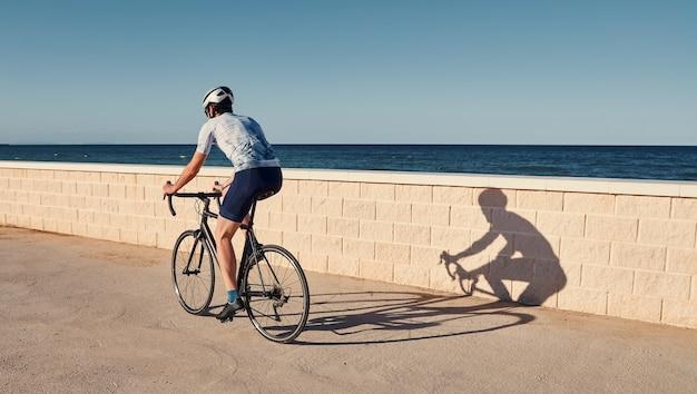 Jonge man rijdt op een racefiets met uitzicht op de zee
