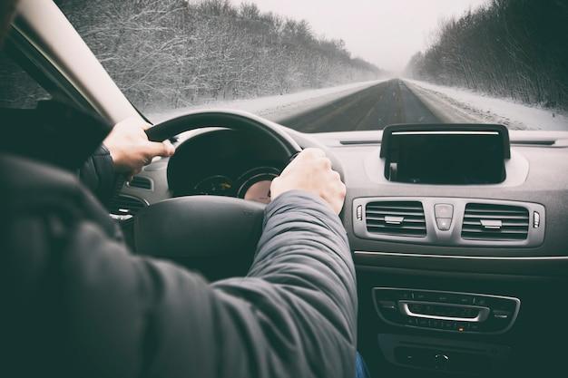 Jonge man rijdt op zijn auto door een besneeuwde weg