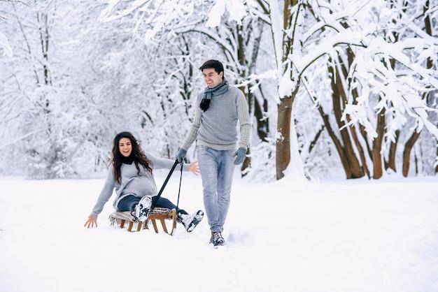 Jonge man rijdt zijn mooie zwangere vrouw in houten rodelen in de sneeuw in het park