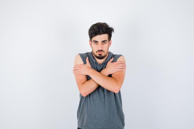 Jonge man rillend van de kou in grijs t-shirt en serieus kijkend