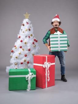 Jonge man rond kerstcadeautjes op grijs