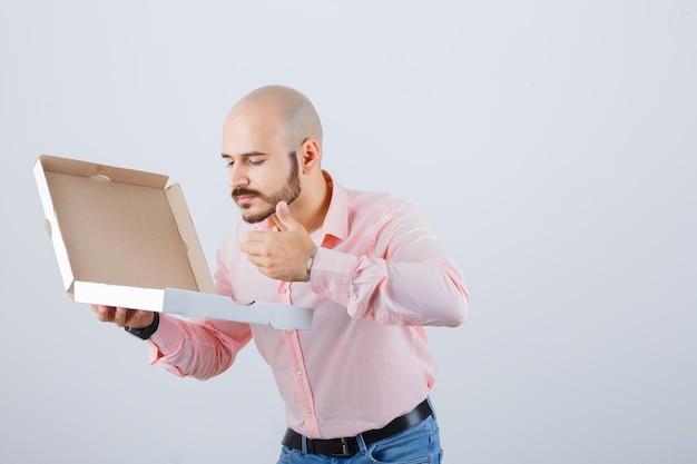 Jonge man ruikt geopende pizzadoos in shirt, spijkerbroek en ziet er heerlijk uit, vooraanzicht.
