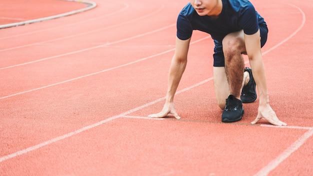Jonge man runner op het startpunt op racebaan