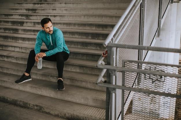 Jonge man rusten tijdens de training met fles water in stedelijke omgeving
