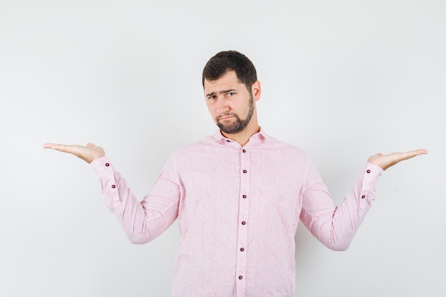 Jonge man schalen gebaar maken in roze shirt en op zoek somber