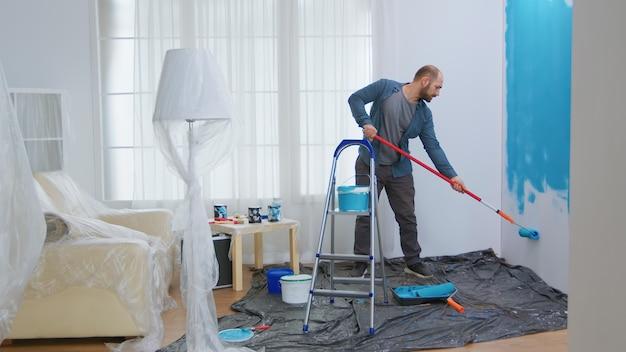 Jonge man schildert muur met rolborstel terwijl hij zijn appartement renoveert. klusjesman herinrichting en woningbouw tijdens renovatie en verbetering. reparatie en decoreren.