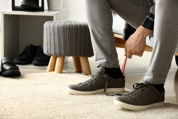 Jonge man schoenen aantrekken in de kleedkamer