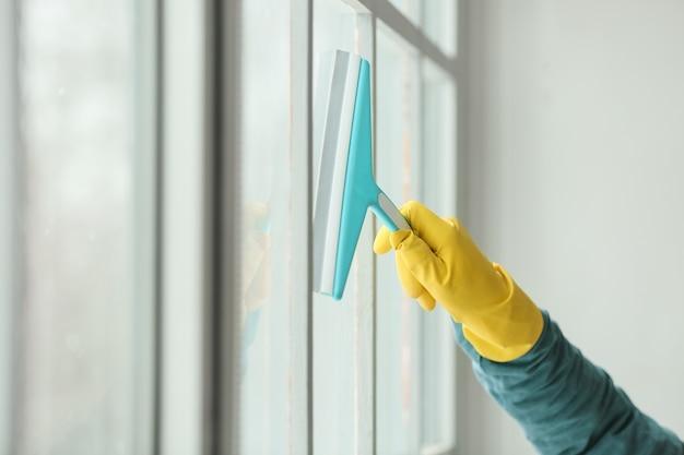 Jonge man schoonmaak venster thuis