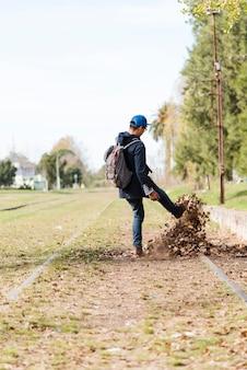 Jonge man schoppen bladeren op treinrails