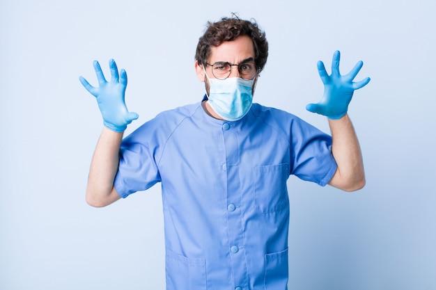 Jonge man schreeuwen in paniek of woede, geschokt, doodsbang of woedend, met de handen naast het hoofd. coronavirus concept