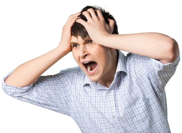 Jonge man schreeuwen met zijn handen op zijn hoofd