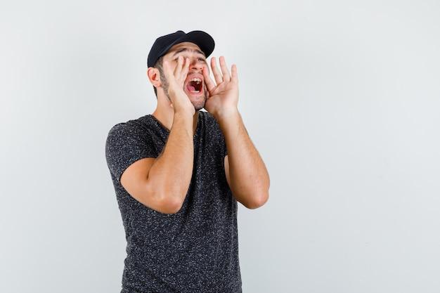 Jonge man schreeuwen of iets in t-shirt en pet aankondigen