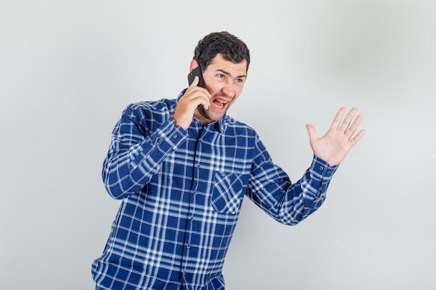 Jonge man schreeuwen op telefoon met stopbord in ingecheckte shirt en op zoek nerveus
