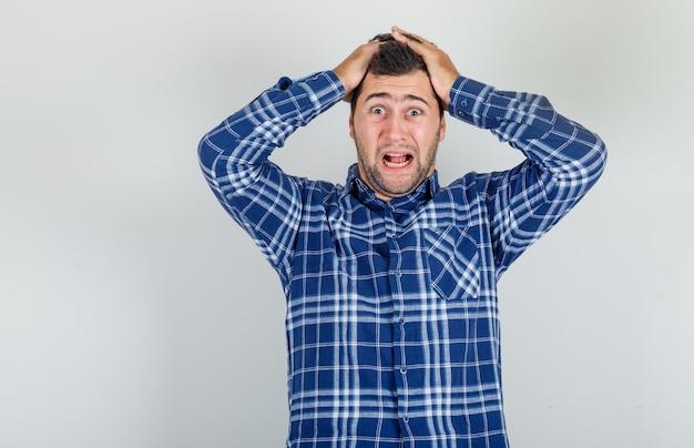 Jonge man schreeuwen terwijl hij zijn hoofd vasthoudt met de handen in een geruit overhemd en op zoek doodsbang