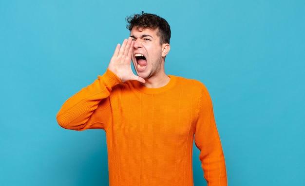 Jonge man schreeuwt luid en boos om ruimte aan de zijkant te kopiëren, met de hand naast de mond