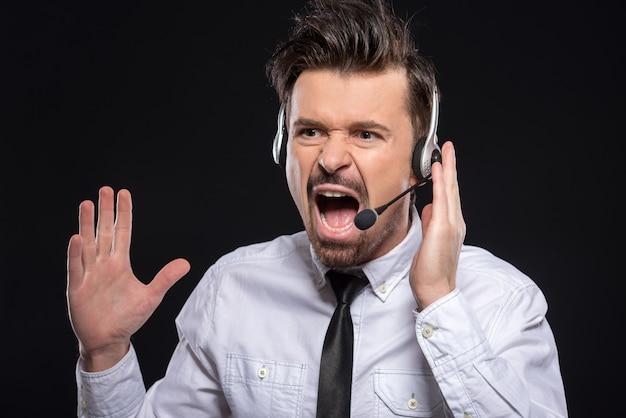 Jonge man schreeuwt met een koptelefoon en microfoon.