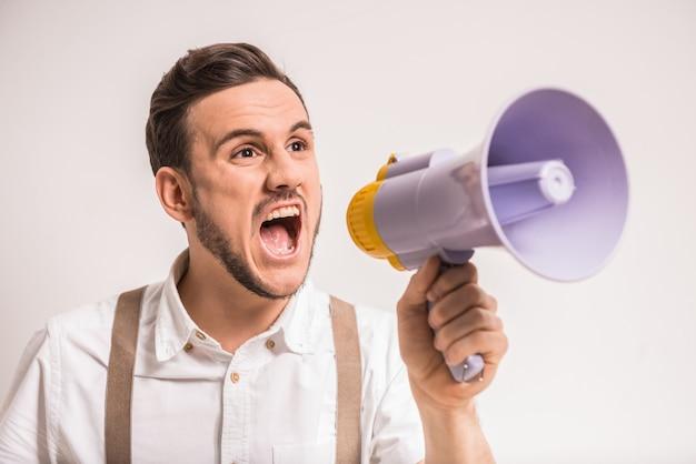 Jonge man schreeuwt over in een megafoon.