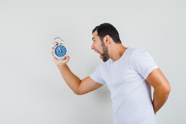 Jonge man schreeuwt terwijl hij naar de klok in wit t-shirt kijkt en in paniek kijkt, vooraanzicht.