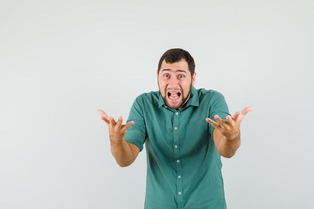 Jonge man schreeuwt terwijl hij zijn handen op een agressieve manier opheft in groen shirt, vooraanzicht.