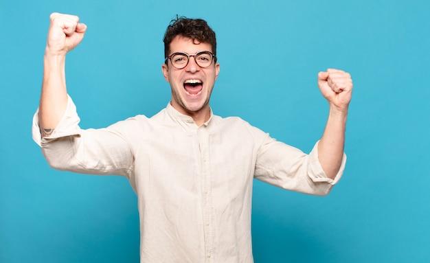 Jonge man schreeuwt triomfantelijk, ziet eruit als opgewonden, blij en verrast winnaar, viert