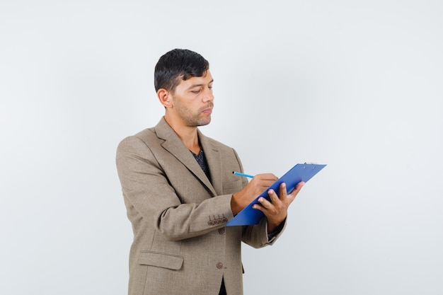 Jonge man schrijft iets in grijsachtig bruin jasje, zwart shirt en ziet er intelligent uit, vooraanzicht.