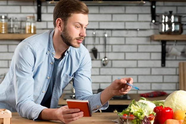 Jonge man schrijven boodschappenlijstje in de keuken