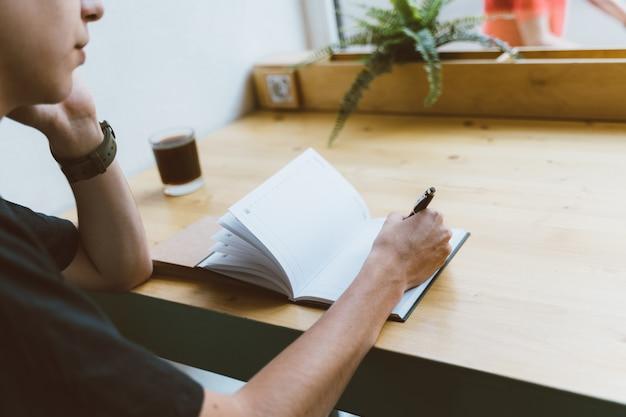 Jonge man schrijven van informatie naar kladblok en sprekende mobiele telefoon, tiener plant een schema