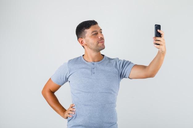 Jonge man selfie met hand op taille in grijs t-shirt.