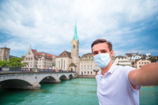 Jonge man selfie te nemen in de oude europese stad nemen selfie. een gezichtsmasker dragen ter voorkoming van coronavirus
