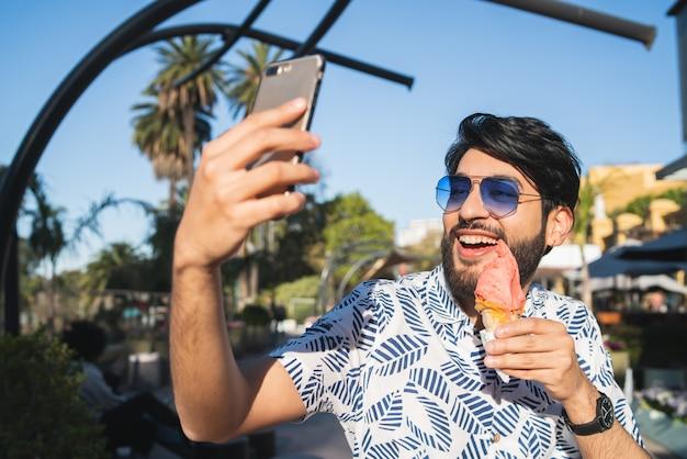 Jonge man selfie te nemen tijdens het eten van ijs.