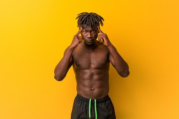 Jonge man shirtless dragen zwempak gericht op een taak, houdt hem wijsvingers hoofd wijzen.