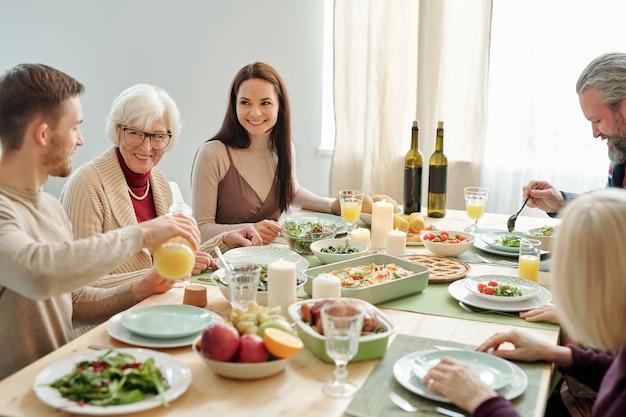 Jonge man sinaasappelsap gieten voor zijn oma tijdens familiediner door feestelijke tafel geserveerd op thanksgiving day