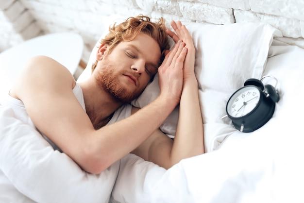 Jonge man slaapt onder een witte deken. zoete dromen.